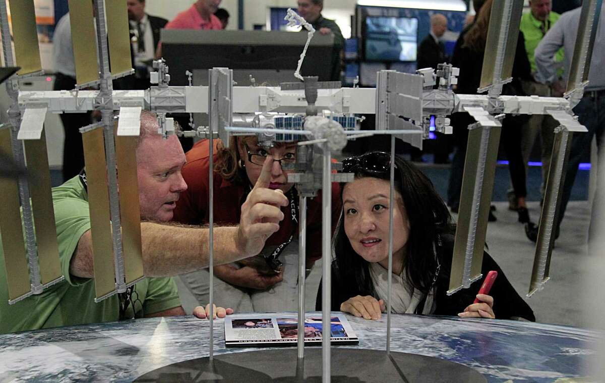 NASA's Kyle Herring points out popular photo spots on the International Space Station to Linda Liu, right, as Rose Herrera looks on.