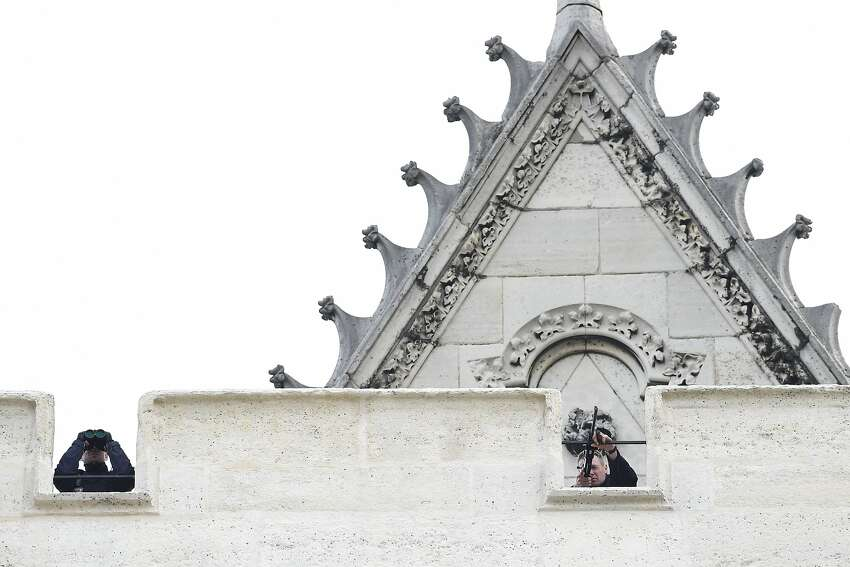 Snipers of the French police are pictured on the roof of a church in the northern Paris suburb of Saint-Denis city center, on November 18, 2015, to secure the area after French Police special forces raid an apartment, hunting those behind the attacks that claimed 129 lives in the French capital five days ago. At least one person was killed in an apartment targeted in the operation aimed at the suspected mastermind of the attacks, Belgian Abdelhamid Abaaoud, and police had been wounded in the shootout.
