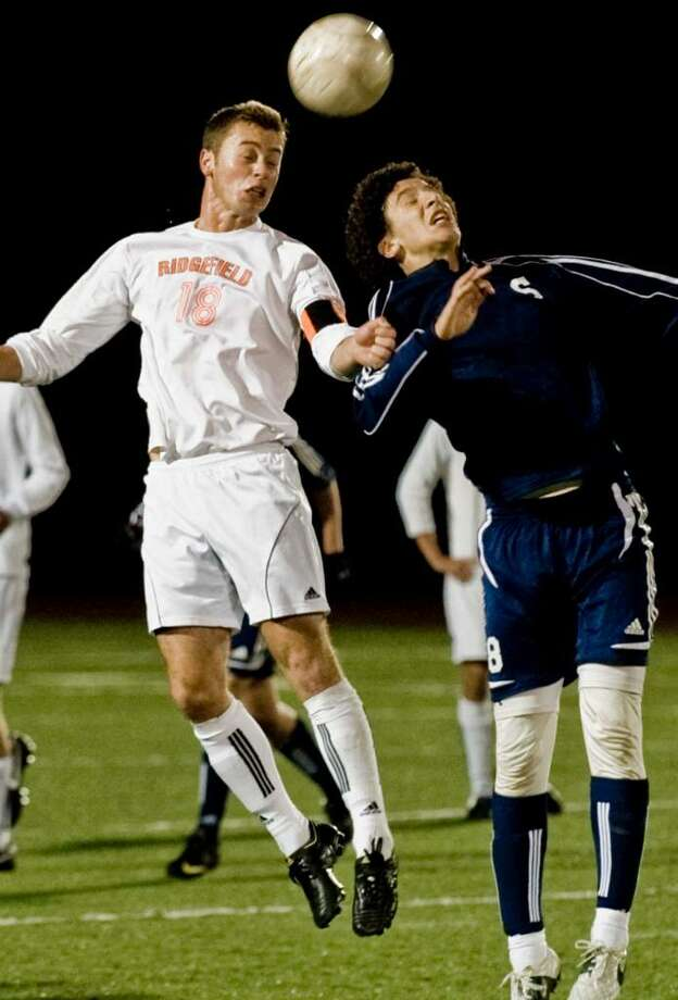 Ridgefield senior Rex Messing and Staples senior Mickey Fitzgerald collide heading the ball in a boys soccer game at Ridgefield. Friday, Oct. 16, 2009 Photo: Scott Mullin / The News-Times
