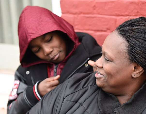 Avery Moses, 6, sitting with his mother after he alerted sleeping residents to a fire in the apartment building where they lived in Albany's South End. Firefighters said no one was injured in the blaze at 50 Broad St. (Skip Dickstein / Times Union)