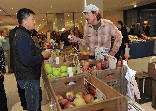 Karl Yang Latham, left, buys some apples from Paul Smith of Little River Farm during the Harvest Festival at the Concourse of the Empire State Plaza on Wednesday, Nov. 18, 2015 in Albany, N.Y.  (Lori Van Buren / Times Union) Photo: Lori Van Buren / 00034250A