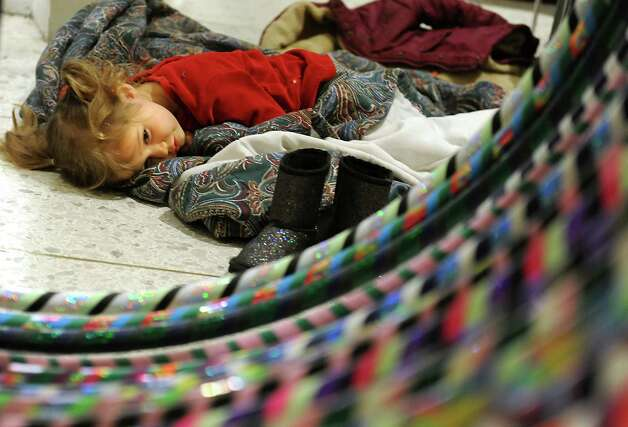 Melody Mapes, 3, of Selkirk lays down for a nap as her mom sells hula hoops during the Harvest Festival at the Concourse of the Empire State Plaza on Wednesday, Nov. 18, 2015 in Albany, N.Y.  (Lori Van Buren / Times Union) Photo: Lori Van Buren / 00034250A