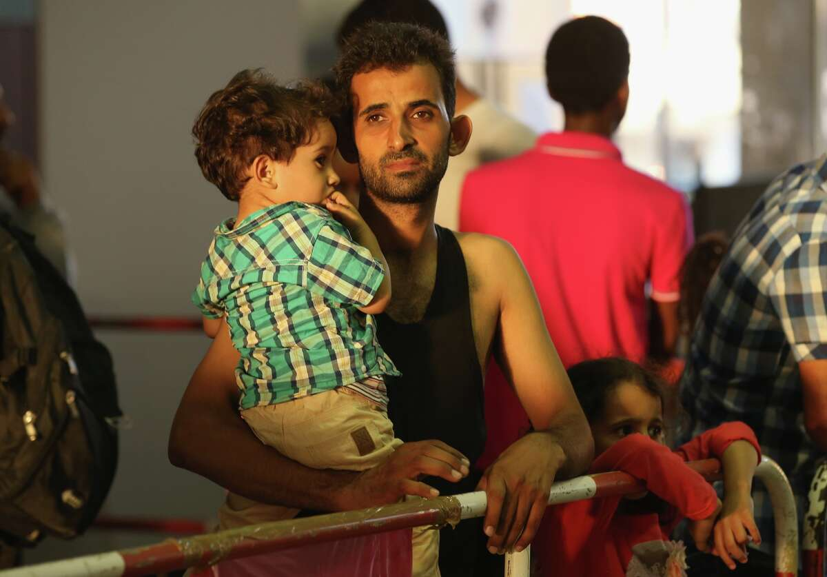 A migrant from Syria holds one of his children in a holding area after arriving at Munich Hauptbahnhof main railway station and being detained by police on August 29, 2015 in Munich, Germany.