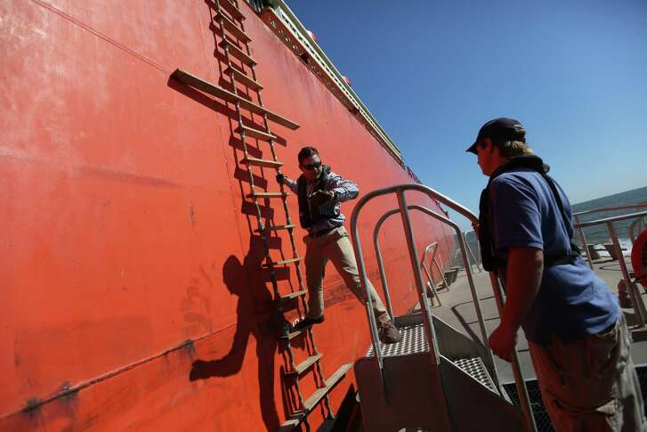 Pilot Tyler Parker makes his way from a barge onto a pilot boat in the Houston Ship Channel.