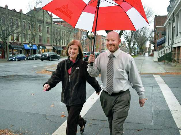 Co-workers Judy Pierce and Joe Bills share an umbrella as rain begins to fall Thursday Nov. 19, 2015 in Saratoga Springs, NY.  (John Carl D'Annibale / Times Union) Photo: John Carl D'Annibale