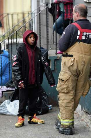 Avery Moses, 6, speaks with an Albany Fire Department official Thursday morning Nov. 19, 2015 after he saved numerous lives by alerting his family to the smell of smoke at his home at 50 Broad Street in Albany, N.Y.     (Skip Dickstein/Times Union) Photo: SKIP DICKSTEIN