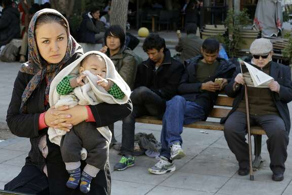 An Afghan woman holds a baby as other migrants sit on a bench with a local resident who reads a newspaper at Victoria square, where hundreds migrants and refugees stay temporarily before trying to continue their trip to more prosperous northern European countries, in Athens, Tuesday, Nov. 10, 2015.  More than 770,000 people have arrived in the EU by sea so far this year overwhelming border authorities and receptions centers. (AP Photo/Thanassis Stavrakis)