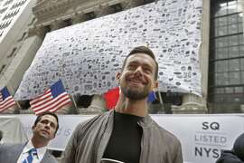 Square CEO Jack Dorsey, foreground, visits outside the New York Stock Exchange before opening bell ceremonies, Thursday, Nov. 19, 2015. Square, the 6-year-old startup known for its white, cube-shaped card readers that plug into smartphones, is surging in its first day as a publicly traded company. (AP Photo/Richard Drew)
