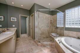 Dual vanities, a jetted tub and walk-in stall shower highlight the master bathroom.
