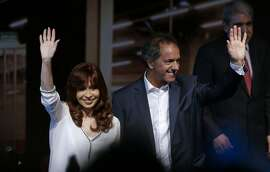 In this Nov. 6, 2015 photo, Argentina's President Cristina Fernandez, left, and her chosen successor Daniel Scioli wave to supporters during a ceremony at the Science and Technology Center in Buenos Aires, Argentina. Fernandez's chosen successor, Scioli, presents himself as the continuation of her policies, while promising to make fixes where necessary.