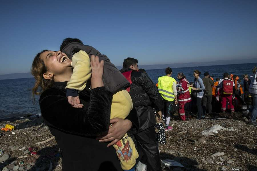 A Syrian refugee rejoices after arriving on an overcrowded raft to the island of Lesbos, Greece, on Nov. 12, 2015. Photo: Paula Bronstein, Getty Images