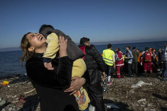 A Syrian refugee rejoices after arriving on an overcrowded raft to the island of Lesbos, Greece on November 12, 2015. Dozens of rafts and boats are still making the journey daily via the Aegean Sea, over 590,000 people have crossed into the gateway of Europe. Nearly all of those are from the war zones of Syria, Iraq and Afghanistan.