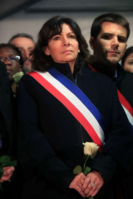 Paris' mayor Anne Hidalgo holds a flower during a rally outside the Stade de France stadium, in Saint-Denis, north of Paris, Thursday, Nov. 19, 2015. The Belgian extremist suspected of masterminding the deadly attacks in Paris died along with his cousin when police stormed a suburban apartment building, French officials said Thursday, a day after the chaotic, bloody raid. (AP Photo/Thibault Camus) Photo: Thibault Camus, Associated Press