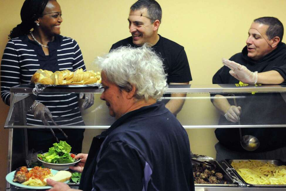 Albany police personnel ShellyAnn Fallen, left, Officer Dan Webster and Sgt. Pat DeLuca serve a pasta lunch to residents at the Interfaith Partnership for the Homeless on Thursday Nov. 19, 2015 in Albany, N.Y. All food was donated by Hannaford Supermarkets. (Michael P. Farrell/Times Union)