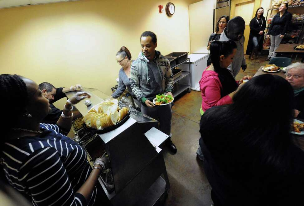 Albany police personnel serve a pasta lunch to resident at the Interfaith Partnership for the Homeless on Thursday Nov. 19, 2015 in Albany, N.Y. All food was donated by Hannaford Supermarkets. (Michael P. Farrell/Times Union)