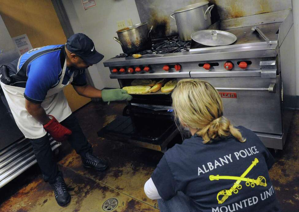 Albany police Officer Gary Tucker checks the garlic bread as he and other police personnel cooked and served a pasta lunch to residents at the Interfaith Partnership for the Homeless on Thursday Nov. 19, 2015 in Albany, N.Y. All food was donated by Hannaford Supermarkets. (Michael P. Farrell/Times Union)