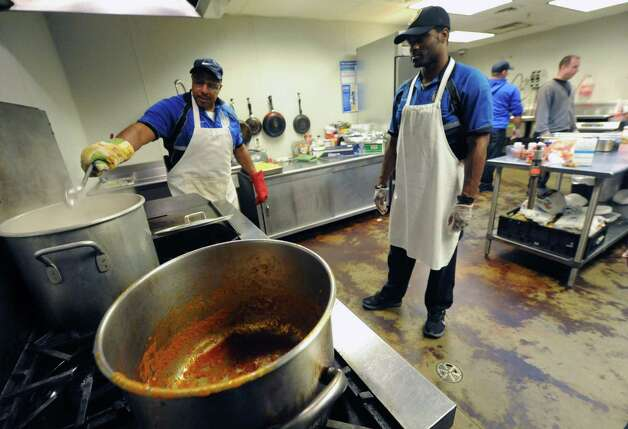 Albany police officer Gary Tucker, left, and officer William Pierce with other police personnel cooked and served a pasta lunch to residents at the Interfaith Partnership for the Homeless on Thursday Nov. 19, 2015 in Albany, N.Y.  All food was donated by Hannaford Supermarkets. (Michael P. Farrell/Times Union) Photo: Michael P. Farrell / 10034368A