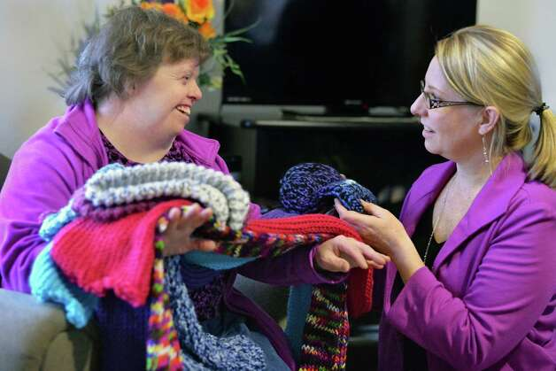 Living Resources Day Program participant Theresa Meehan, left, of Clifton Park shows hats and scarves she and others made to Cindy Harrington, Director of Development and Marketing for Shelters of Saratoga, as Living Resources present Shelters with more than 50 hand-knit winter hats and scarves for the homeless Thursday Nov. 19, 2015 in Saratoga Springs, NY.  (John Carl D'Annibale / Times Union) Photo: John Carl D'Annibale / 10034344A