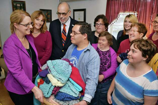 Director of Development and Marketing for Shelters of Saratoga Cindy Harrington, left, receives more than 50 hand-knit winter hats and scarves for the homeless from Living Resources Day Program participants Thursday Nov. 19, 2015 in Saratoga Springs, NY. At top are Alta Schalehn Living Resources board VP and Fred Erlich, CEO of Living Resources. (John Carl D'Annibale / Times Union) Photo: John Carl D'Annibale / 10034344A