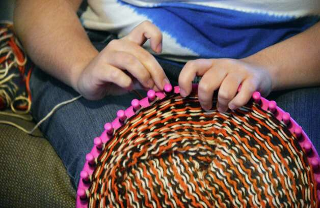 A Living Resources Day Program participant  makes a hat during their visit to Shelters of Saratoga as Living Resources present Shelters with more than 50 hand-knit winter hats and scarves for the homeless Thursday Nov. 19, 2015 in Saratoga Springs, NY.  (John Carl D'Annibale / Times Union) Photo: John Carl D'Annibale / 10034344A