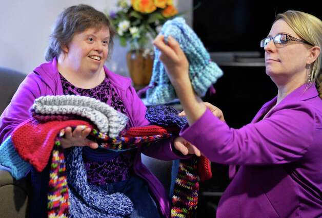 Living Resources Day Program participant Theresa Meehan, left, of Clifton Park shows hats and scarves she and others made to Cindy Harrington, Director of Development and Marketing for Shelters of Saratoga as Living Resources present Shelters with more than 50 hand-knit winter hats and scarves for the homeless Thursday Nov. 19, 2015 in Saratoga Springs, NY.  (John Carl D'Annibale / Times Union) Photo: John Carl D'Annibale / 10034344A