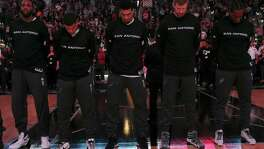 San Antonio Spurs' Danny Green, center, bows his head during the National Anthem before their game against the Denver Nuggets  at the AT&T Center, Wednesday, Nov. 18, 2015.