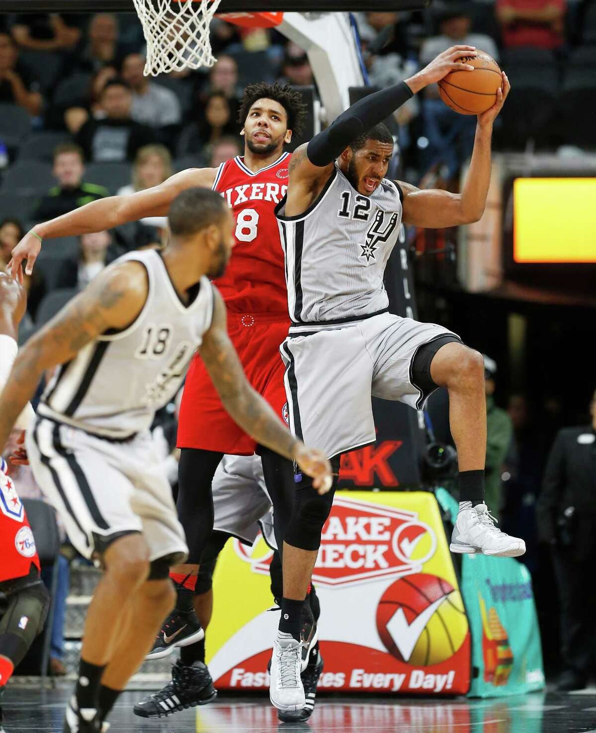 Spurs' LaMarcus Aldridge (12) steals away a pass against the Philadelphia 76ers Jahlil Okafor (08) at the AT&T Center on Saturday, Nov. 14, 2015. Spurs defeated the Sixers, 92-83. (Kin Man Hui/San Antonio Express-News)