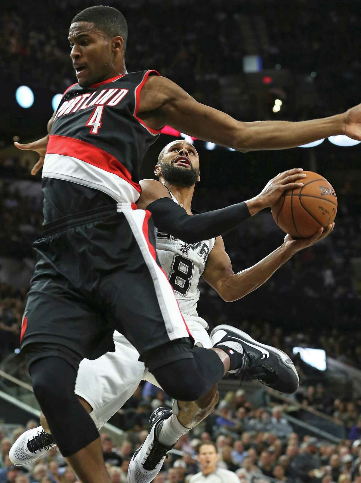 Patty Mills tries to angle around Maurice Harkless on a fast break as the Spurs host Portland at the AT&T Center on November 16, 2015.