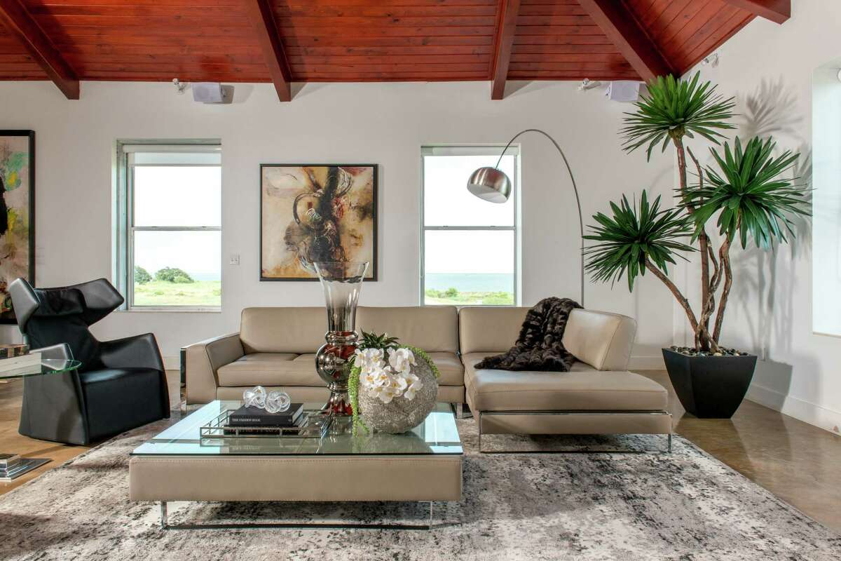 """The Seureaus wanted their living space """"to be very functional for them to entertain family and friends,"""" says designer Angela Watson. High ceilings and polished concrete floors are accessorized with sound-absorbing rugs."""