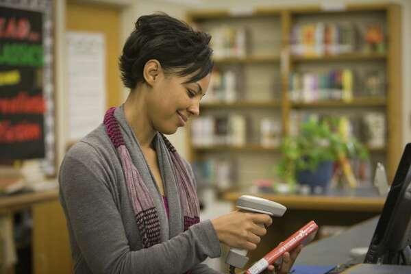 Mixed race librarian checking out book in library