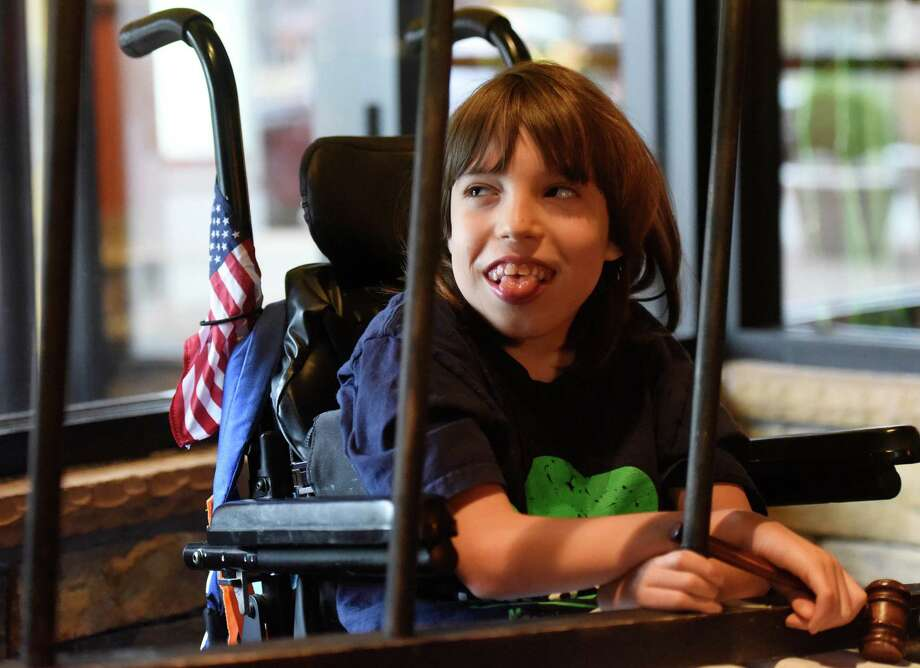 """Dakota Fortier, 11, of Waterbury, laughs while behind bars during the Muscular Dystrophy Association's Lock-Up fundraising event at Kona Grill in Stamford. Business and community leaders in the Stamford area became """"jailbirds"""" as they attempted to raise """"bail money"""" through online funding and on-the-spot donations. The MDA does six lockups per year and this was its third in Stamford. The group hoped to raise $50,000 at the event. Photo: Tyler Sizemore / Hearst Connecticut Media / Greenwich Time"""