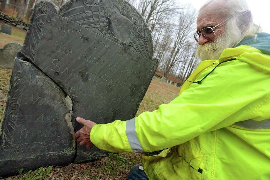 Robert Paradise, caretaker of Redding's six public cemeteries, points out the damage on the headstone of Samuel Sanford at Barlow Cemetery on Great Pasture Road Thursday. The town is trying to decide how to fund the restoration of three historic headstones and better maintain their historic cemeteries. Photo: Autumn Driscoll / Hearst Connecticut Media / Connecticut Post