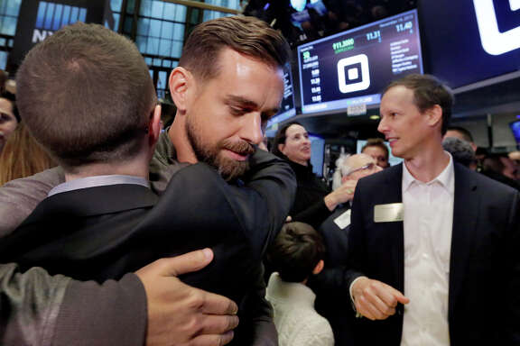 Square CEO Jack Dorsey gets a hug at the New York Stock Exchange after shares begin trading. Square co-founder Jim McKelvey is at right.
