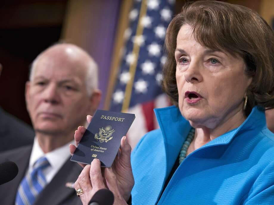 Senate Intelligence Committee Vice Chair Sen. Dianne Feinstein, D-Calif.,  joined by Sen. Ben Cardin, D-Md., left, points to the embedded chip in her passport that contains digital information, as she and other Democrats talk about security measures for Syrian refugees and others coming into the U.S., Thursday, Nov. 19, 2015, during a news conference on Capitol Hill in Washington. (AP Photo/J. Scott Applewhite) Photo: J. Scott Applewhite, Associated Press