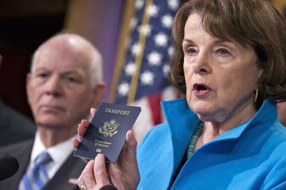 Senate Intelligence Committee Vice Chair Sen. Dianne Feinstein, D-Calif.,  joined by Sen. Ben Cardin, D-Md., left, points to the embedded chip in her passport that contains digital information, as she and other Democrats talk about security measures for Syrian refugees and others coming into the U.S., Thursday, Nov. 19, 2015, during a news conference on Capitol Hill in Washington. (AP Photo/J. Scott Applewhite)