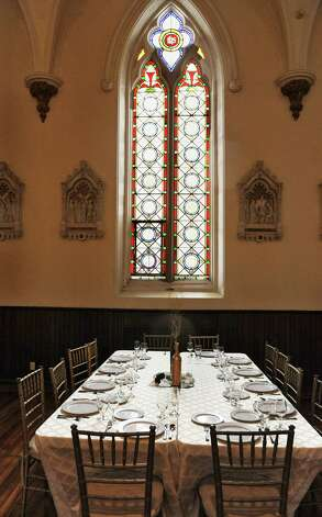 A table setting under a stained glass window at Dan and Jennifer O'Neill's The Venue at St. Joseph's, a renovated church now an event space Wednesday Nov. 11, 2015 in Cohoes, NY.  (John Carl D'Annibale / Times Union) Photo: John Carl D'Annibale / 00034138A