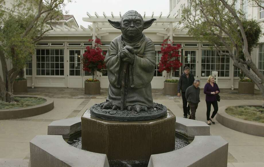 People walk past a Yoda fountain outside Lucasfilm headquarters in San Francisco in 2012. Photo: Jeff Chiu, Associated Press