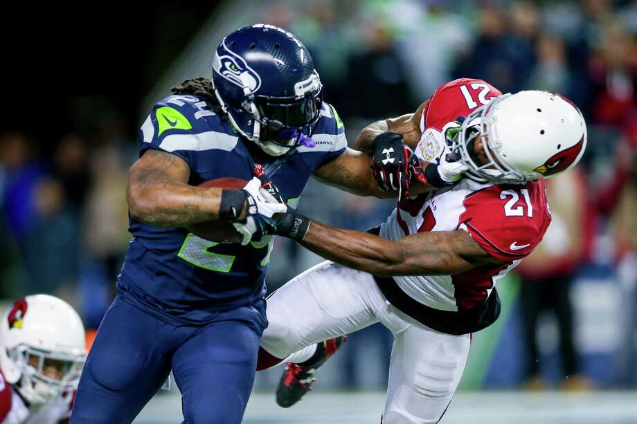 Seahawks running back Marshawn Lynch stiff arms Arizona's Patrick Peterson after a 10-yard gain in the first quarter of the Seattle Seahawks-Arizona Cardinals game at CenturyLink Field in Seattle on Sunday November 15, 2015. Photo: Scott Eklund, Seattlepi.com / Red Box Pictures 3131 Western Ave. Suite 323 Seattle, WA 98121