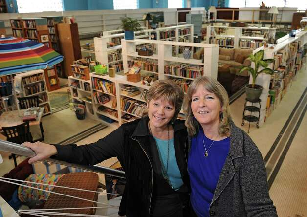 Roberta Sandler, left, and her partner in Grassroots Givers Mary Partridge-Brown stand in front of donated goods at the Grassroots Givers headquarters on Wednesday, Nov. 18, 2015 in Albany, N.Y. The building used to house the Albany YMCA. (Lori Van Buren / Times Union) Photo: Lori Van Buren / 10034304A