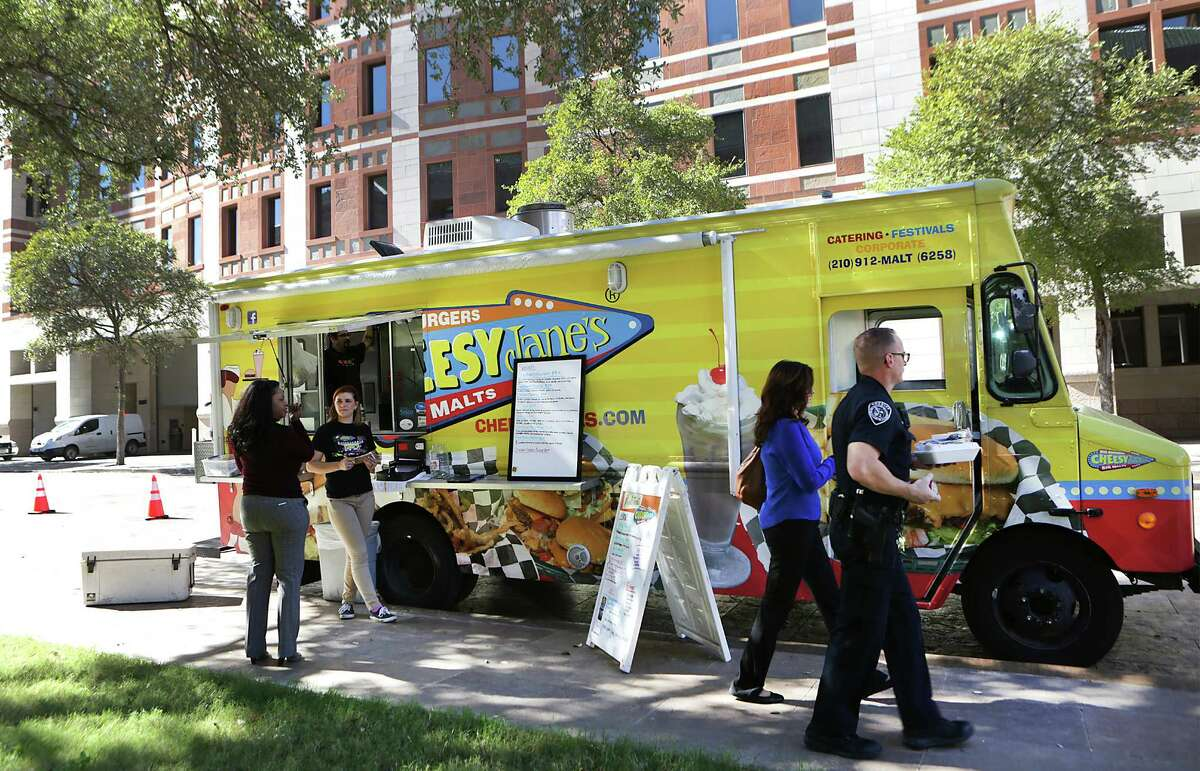 Food truck patrons pickup meals at the Cheesy Jane's truck next to the Justice Center. The City Council will decide on Thursday, Nov. 19, 2015, whether or not to allow food trucks to operate within 300 feet of brick-and-morter restaurants.