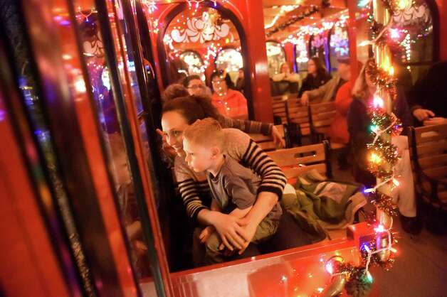 Sawyer Goodermote, 4, of Petersburgh, center, sits with his mother, Vallis Goodermote, as take a trolley ride to view the 19th annual Price Chopper Capital Holiday Lights in the Park on Thursday, Nov. 19, 2015, at Washington Park in Albany, N.Y. Hours are Sundays through Thursdays from 6 to 9 p.m. and Fridays and Saturdays from 6 to 10 p.m. (Cindy Schultz / Times Union) Photo: Cindy Schultz / 00034235A