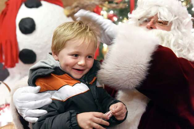 Keegan Broderick, 4, of Albany, left, gets a candy cane and a pat on the head from Santa during the 19th annual Price Chopper Capital Holiday Lights in the Park on Thursday, Nov. 19, 2015, at Washington Park in Albany, N.Y. Hours are Sundays through Thursdays from 6 to 9 p.m. and Fridays and Saturdays from 6 to 10 p.m. (Cindy Schultz / Times Union) Photo: Cindy Schultz / 00034235A