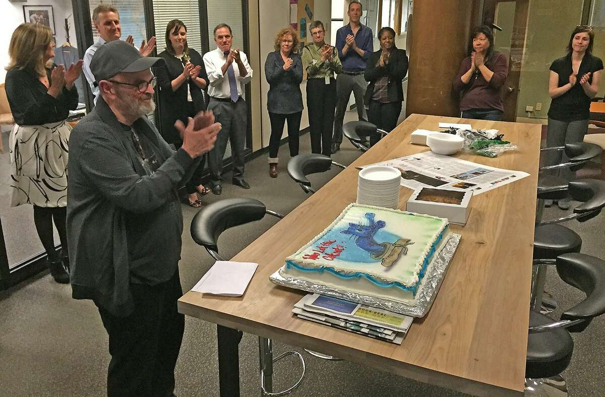A cake is presented to Columnist Jon Carroll Thursday, November 19, 2015 who retired from the San Francisco Chronicle after 33 years working at the newspaper.