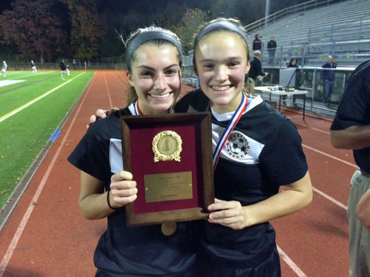 FILE PHOTO: Morgan Hartmayer, left, and Sarah Battipaglia of Ridgefield High enjoy a moment with the FCIAC girls soccer championship trophy.
