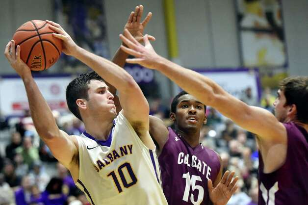 UAlbany's Mike Rowley, left, looks to pass as Colgate's Jordan Swopshire, center, and Sean O'Brien defend during their basketball game on Thursday, Nov. 19, 2015, at SEFCU Arena in Albany, N.Y. (Cindy Schultz / Times Union) Photo: Cindy Schultz / 00034275A