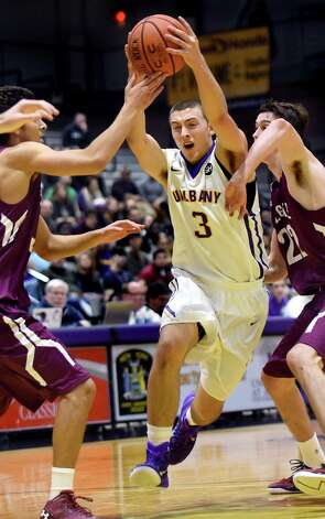 UAlbany's Joe Cremo, center, fights his way to the hoop during their basketball game against Colgate on Thursday, Nov. 19, 2015, at SEFCU Arena in Albany, N.Y. (Cindy Schultz / Times Union) Photo: Cindy Schultz / 00034275A