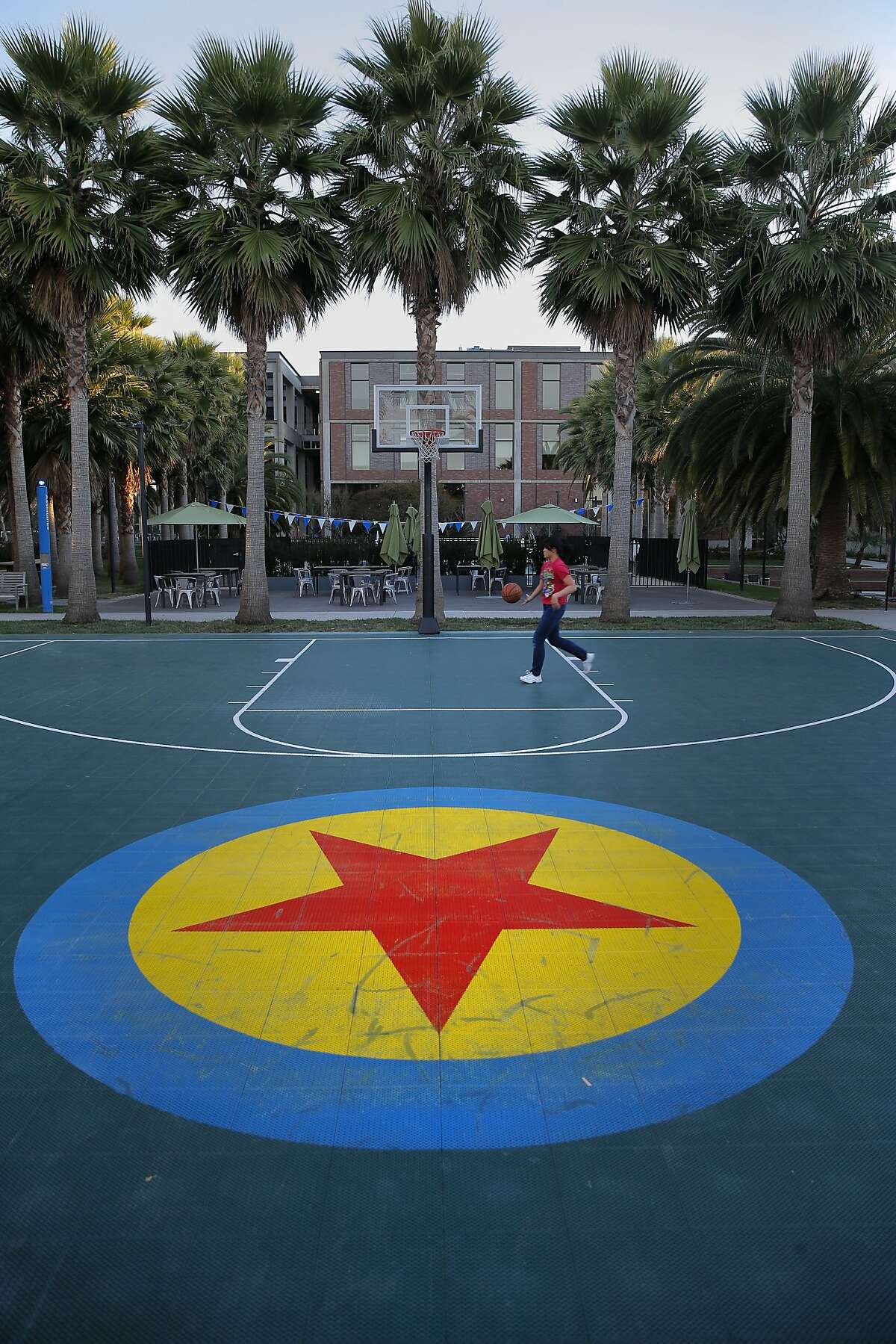 The outdoor basketball court has the Luxo Ball design in center court at the headquarters of the Pixar Animation Studios in Emeryville, Calif., on Thurs. November 19, 2015.