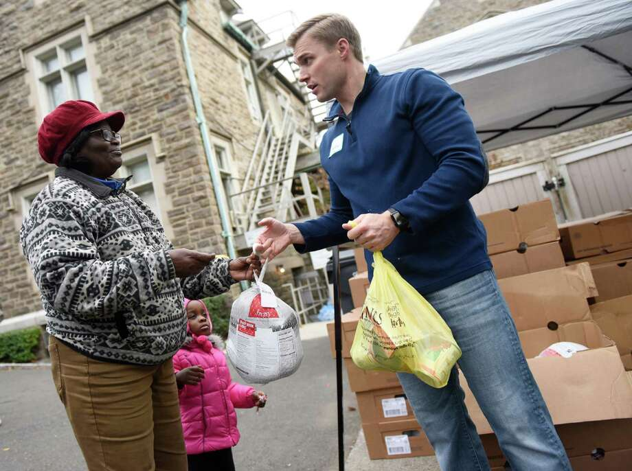 Lourene Dinac, of Stamford, and her granddaughter, Isabelle Petin, receive a frozen turkey and Thanksgiving side dishes from volunteer Andrew Billinghurst at Neighbor to Neighbor in Greenwich, Conn. Thursday, Nov. 19, 2015. 300 turkeys were donated by Kings Food Markets with another 100 donated by St. Michael the Archangel Roman Catholic Church. Additional Thanksgiving food, such as stuffing, cranberry sauce, corn and potatoes, was donated by Berkshire Hathaway. 400 total turkeys were distributed to qualified families on Thursday with another 200 turkeys expected to be distrubted before Thanksgiving. Photo: Tyler Sizemore / Hearst Connecticut Media / Greenwich Time
