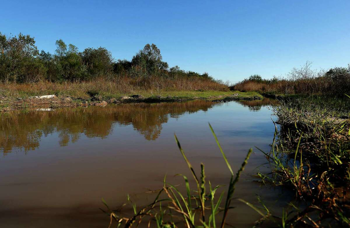 Standing water sits at the southern end of the Buffalo Speedway where it turns to Willowbend Boulevard in the middle of 332 acres where the University of Texas had planned to build a research facility in southwest Houston, Thursday, Nov. 19, 2015, in Houston.