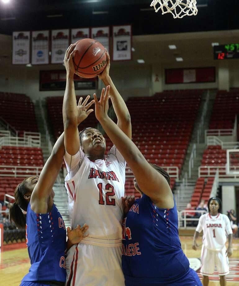 Lamar University's Kiara Desamours battles between Louisiana College's defense as she takes her shot during the Lady Cardinals' home opener Thursday night at the Montagne Center.  Photo taken Thursday, November 19, 2015  Kim Brent/The Enterprise Photo: Kim Brent / Beaumont Enterprise